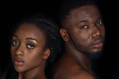 young african american couple with water drops on faces looking at camera isolated on black