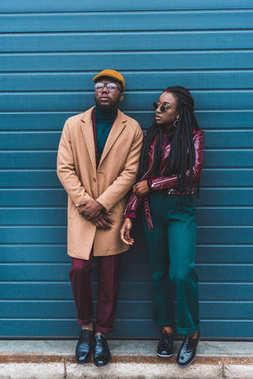 full length view of stylish african american couple in jacket and overcoat standing together outside