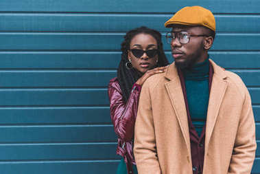 beautiful stylish young african american couple in jacket and overcoat posing together outside