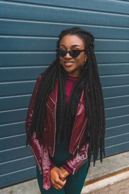 beautiful smiling young african american woman in jacket and sunglasses posing on street