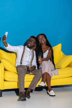 happy stylish young african american couple holding glasses of wine and taking selfie with smartphone on sofa