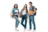 multikulturní studenti při pohledu na fotoaparát s knihami a basketbalový míč izolované na bílém