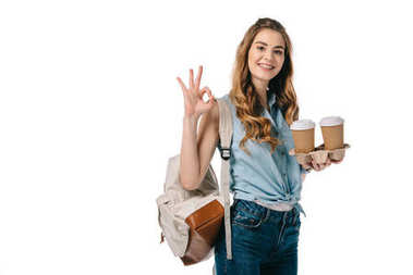 beautiful student showing okay gesture and holding coffee isolated on white