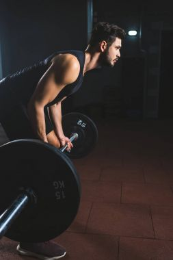 Side view of young bodybuilder holding barbell in sports hall