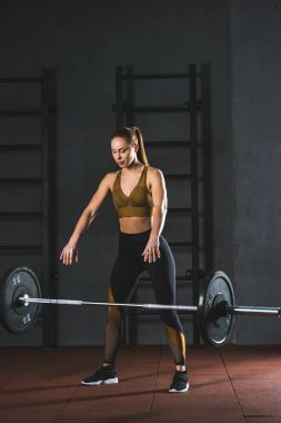 Young caucasian sportswoman letting go barbell  in sports hall