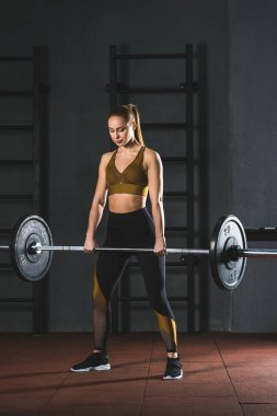 Front view of young sportswoman holding barbell in sports hall