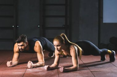 Young sportswoman and sportsman doing push ups in sports hall