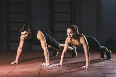 Sportswoman and sportsman doing push ups in gym in sports hall