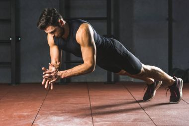 View of young sportsman doing push ups  in sports hall