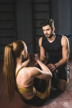Male trainer helping young sportswoman to do abs in gym