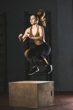 Young sportswoman jumping on wooden block in gym