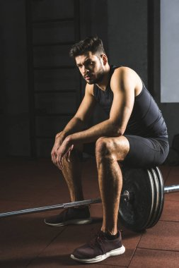 Young caucasian sportsman sitting on barbell in gym