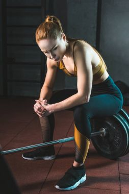 Frustrated young sportswoman sitting on barbell in gym
