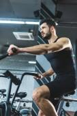 Inquadratura dal basso dello sportsman facendo allenamento sulla bici di esercitazione nel centro sportivo