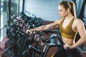 Mladá sportovkyně dělá cvičení na rotopedu ve sportovním centru