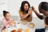 Fotografie manželka a manžel krmení navzájem snídani s dětmi