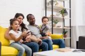 Fényképek fiatal család együtt nézni a tv a nappaliban