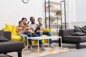 Fényképek boldog fiatal család együtt nézni a tv a nappaliban