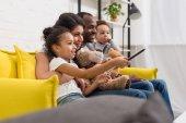 Fényképek gyönyörű fiatal család együtt nézni a tv-t a kanapén