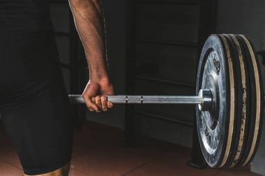 Cropped image of sportsman holding barbell in gym