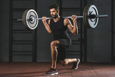 Young sportsman doing exercise with barbell on shoulders in gym