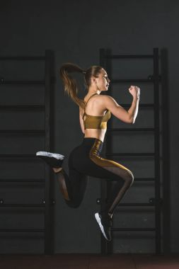 Side view of jumping sportswoman doing cardio exercise in gym