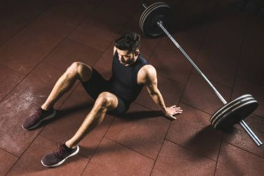 High angle view of resting sportsman sitting near barbell in gym