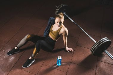 Young sportswoman with towel on shoulder sitting on floor near barbell in gym