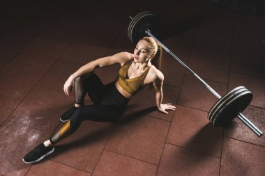 Young sportswoman resting on floor near barbell in gym