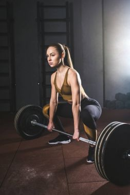 Young sportswoman preparing to raise barbell in gym