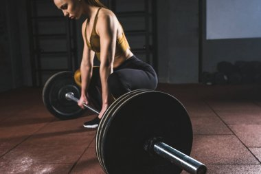 Cropped image of young sportswoman prepare to raise barbell in gym
