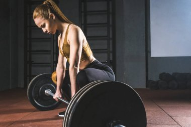 Side view of young sportswoman preparing to raise barbell in gym
