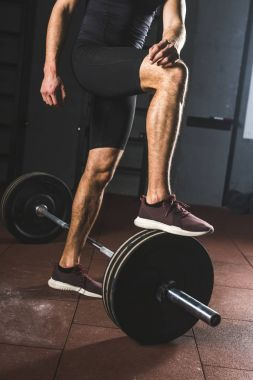 Cropped image of resting sportsman standing on barbell  in gym