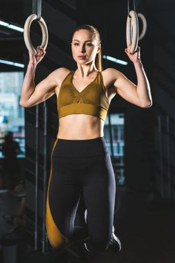 Front view of sportswoman doing exercise on gymnastic rings in sports center