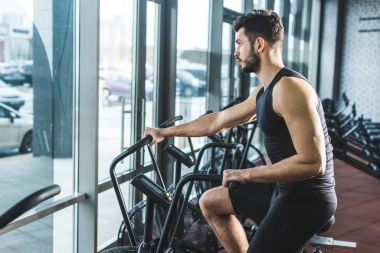 Side view of young sportsman doing workout on exercise bike in sports center