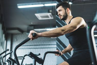 Low angle view of sportsman doing workout on exercise bike in sports center