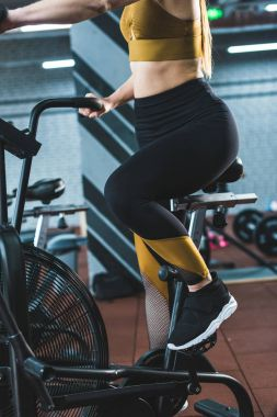 Cropped image of sportswoman doing workout on exercise bike in sports center