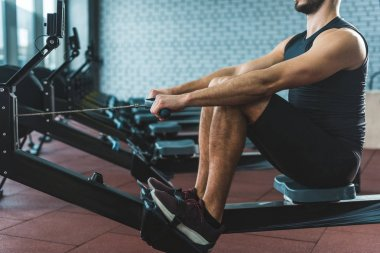 Cropped image of sportsman doing exercise on rowing machine in sports center