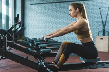 Side view of sportswoman doing exercise on rowing machine in sports center