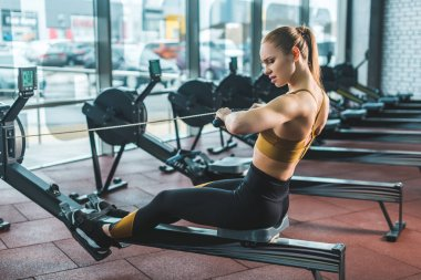 Young sportswoman doing exercise on rowing machine in sports center