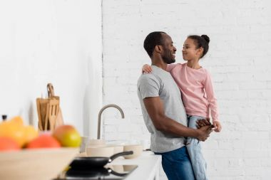 handsome young father holding his daughter at kitchen