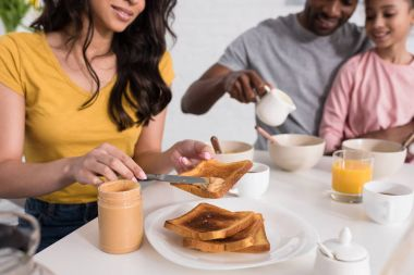 cropped shot of woman applying peanut butter on toasts for husband and daughter