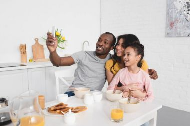 happy young family taking selfie on kitchen while having breakfast