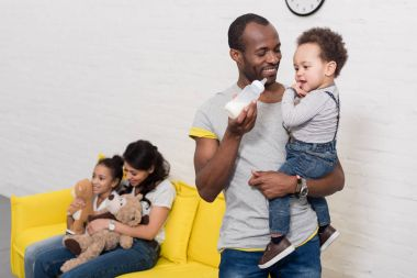 happy parents spending time with kids at home