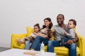 giovane famiglia felice guardare insieme la tv sul divano