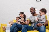 Fényképek boldog fiatal család együtt nézni a tv-t a kanapén