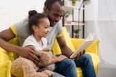 boldog fiatal apa és lánya együtt könyvet olvas otthon