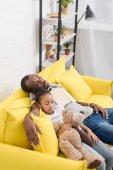 apa és gyönyörű lánya alszik együtt a kanapén mese olvasása után