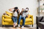 erschrocken afrikanischen amerikanischen Ehepaar in virtual-Reality-Headsets auf couch