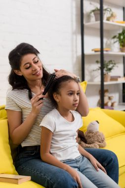 young happy mother combing daughters hair on couch at home